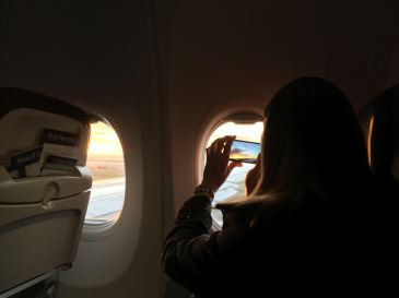 Person looks out airplane window with phone in hand.